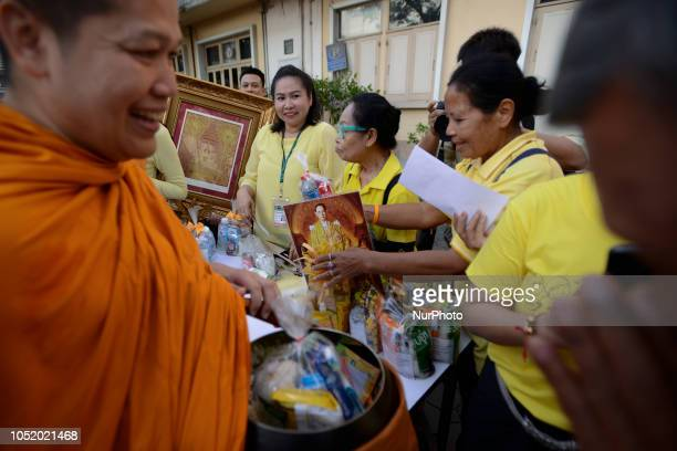 Thais alms to a Buddhist monk during a making 2 year anniversary of the Thai King Bhumibol Adulyadej's death at Siriraj Hospital in Bangkok Thailand...