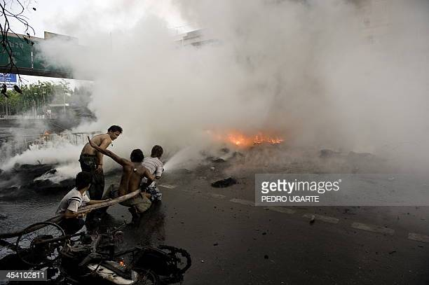 Thais attempt to extinguish a fire caused by a burning barricade during clashes between demonstrators and security forces in Bangkok on May 16 2010...