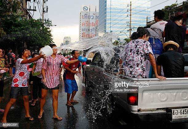 Thais enjoy throwing water at people driving down the street during the water festival called Songkran as the capital city attempts to get back to...