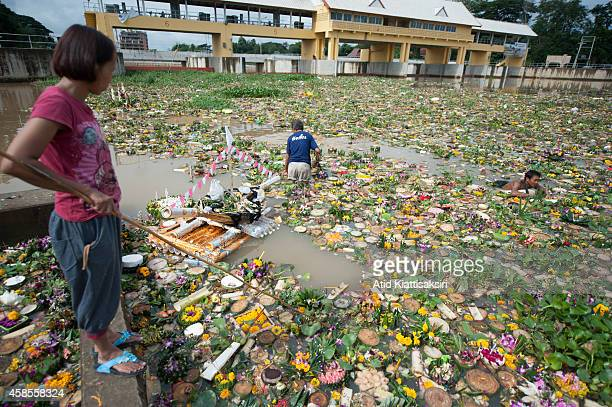 Thais find valuables from thousands of krathongs at a floodgate of the Ping river during the Loy Krathong Festival in Chiang Mai. People place money...