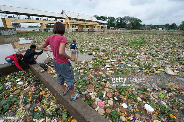 Thais find valuables from thousands of Krathongs at a floodgate of the Ping river during Loy Krathong Festival. People place money along with candles...
