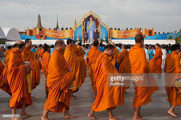 Thais give alms to monks as they celebrate the Thai Queen Sirikit's 84rd birthday at Sanam Luang in front of the Royal Palace, in Bangkok, 12 August...