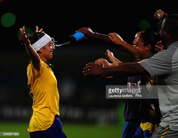 Thais of Brazil gets a squirt in the face from a water bottle as she celebrates scoring the second goal with the substitutes during the FIFA U17...