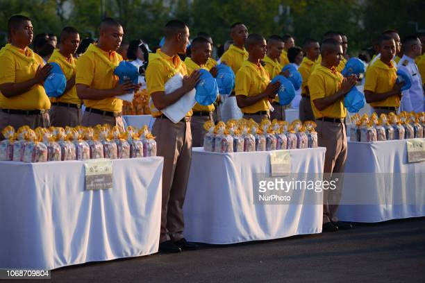 Thais offer alms to Buddhist monks as part of in memory of late Thai King Bhumibol Adulyadej on his birthday anniversary at Sanam Luang in Bangkok...