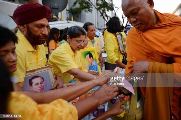 Thais offer alms to Buddhist monks to mark the 2 year anniversary of the Thai King Bhumibol Adulyadej's death at Siriraj Hospital in Bangkok Thailand...