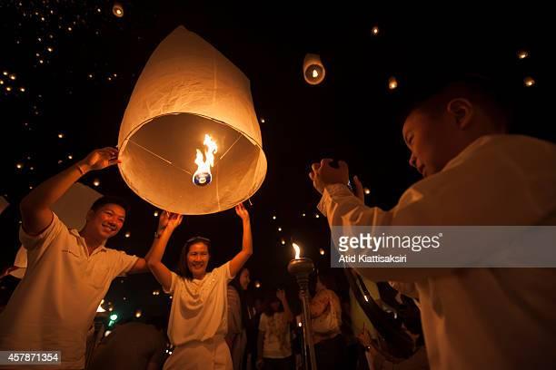 Thais pose for photographs with sky lanterns during Yi Peng Festival at Lanna Dhutanka