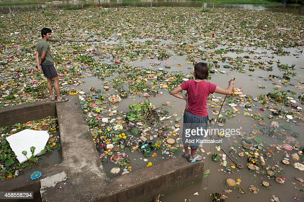 Thais stand on a floodgate to find valuables from krathongs in the Ping river during Loy Krathong Festival in Chiang Mai. People place money along...