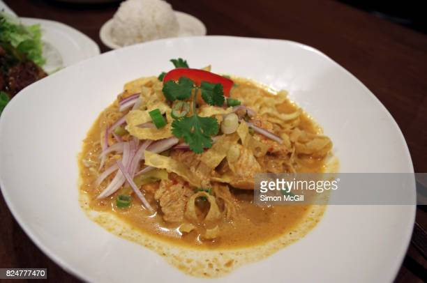 Thai-style chicken yellow curry garnished with fried noodle, raw red onion and coriander leaf