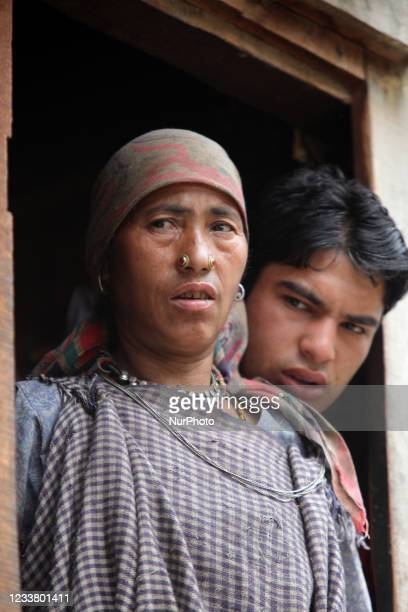 Thakur woman in traditional clothing and her husband stand in the doorway of their home in the Broat Village in Himachal Pradesh, India.