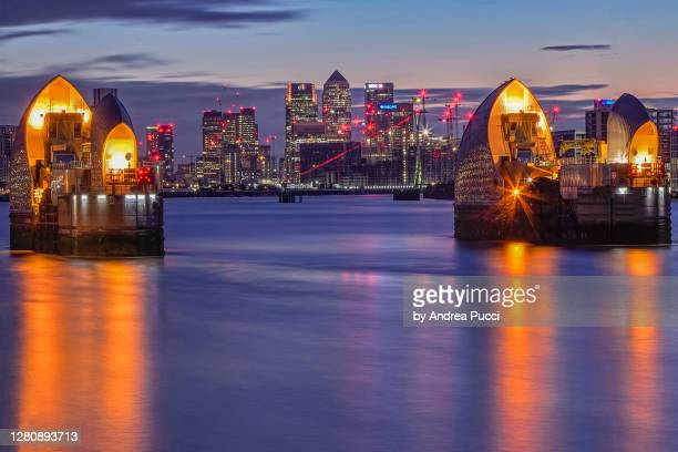 thames barrier and canary wharf, woolwich, london, united kingdom - the o2 england stock pictures, royalty-free photos & images