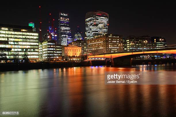 Thames River By Illuminated Buildings In City