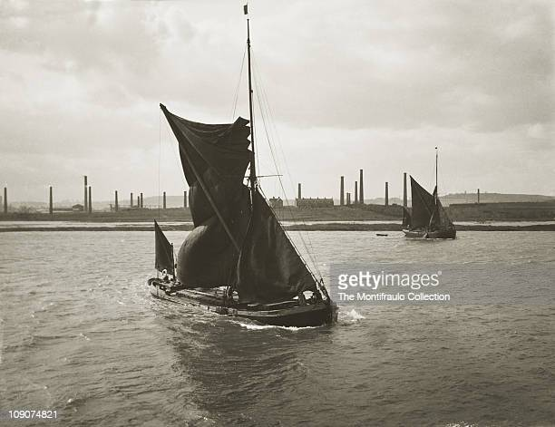 Thames sailing barges at sea one in the process of hoisting sails Chatham Dockyard in the background Chatham Kent England April 1913