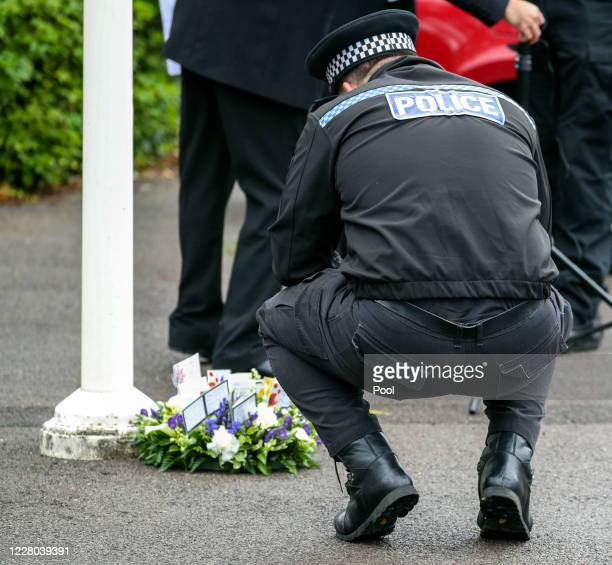 Thames Valley Police officer looks at a floral tribute at the end of a memorial service for Pc Andrew Harper at Newbury Police Station to mark the...