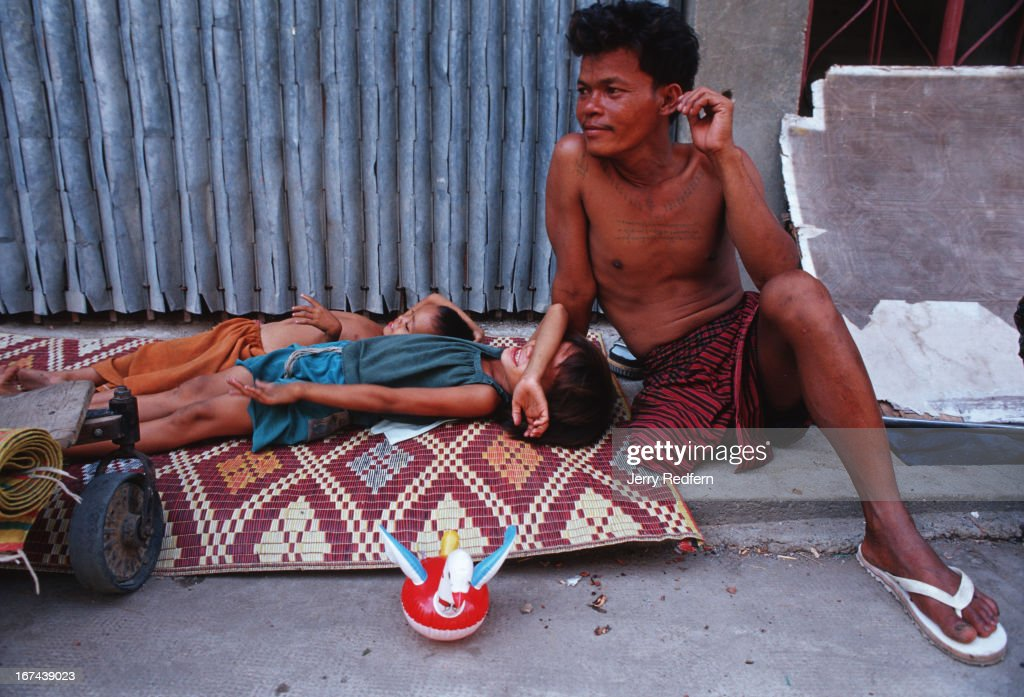 Than Neoun, 38, lives with his wife and daughter (here with a friend) at Wat Ounalom. Than Neoun lost his leg to a mine while fighting for the Cambodian army, was discharged with almost no compensation, and now makes what living he can begging in the streets..