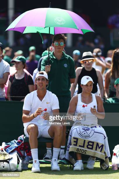 Thanasi Kokkinakis and Ashleigh Barty of Australia look on during a break in play against Fabrice Martin of France and Raluca Olaru of Romania in...
