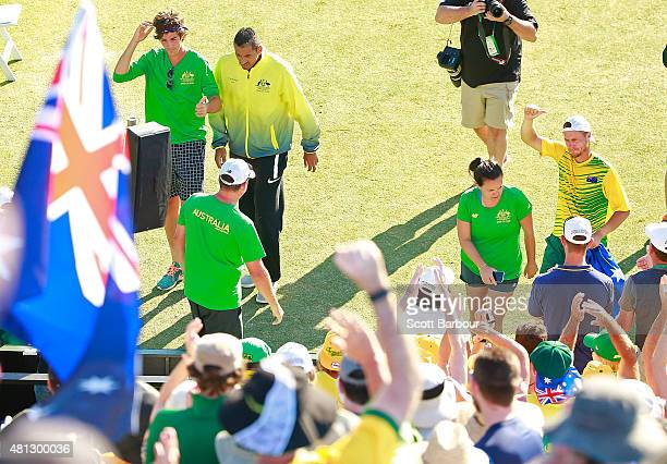 Thanasi Kokkinakis and Nick Kyrgios leave the court as Lleyton Hewitt of Australia celebrates with supporters after winning the reverse singles match...
