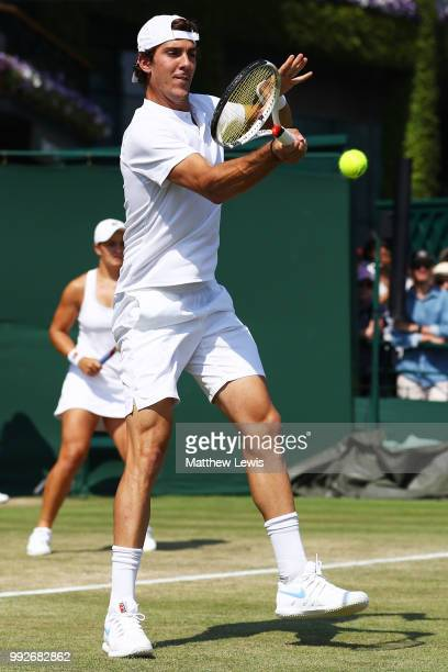Thanasi Kokkinakis of Australia returns a shot against Fabrice Martin of France and Raluca Olaru of Romania during their Mix Doubles first round...