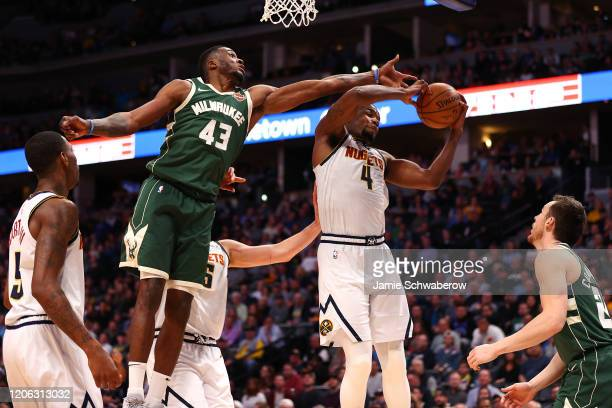 Thanasis Antetokounmpo of the Milwaukee Bucks and Paul Millsap of the Denver Nuggets battle for a rebound at Pepsi Center on March 9 2020 in Denver...
