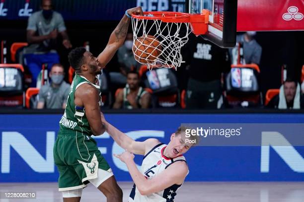 Thanasis Antetokounmpo of the Milwaukee Bucks dunks the ball against Anzejs Pasecniks of the Washington Wizards during the second half at Visa...