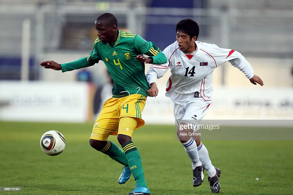 Thanduyise Khuboni (L) of South Africa is challenged by Ri Chol Myong of North Korea during the international friendly match between South Africa and North Korea at the Brita arena on April 22, 2010 in Wiesbaden, Germany.