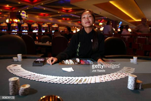Thanee who runs a poker table waits for players May 11 2004 during the grand opening for the Seminole Hard Rock Hotel and Casino in Hollywood Florida...