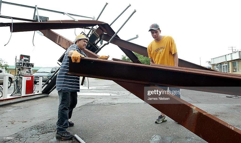 Thanh Ta (L) and Roland Hernandez (R) try to move a gasoline & Claudette Aftermath Assessed By Texans Pictures | Getty Images