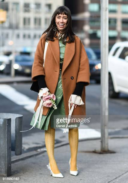 Thania Peck is seen wearing a Moussy coat Cos dress The Kooples belt Dior shoes and a Prada bag outside the Tadashi Shoji show during New York...