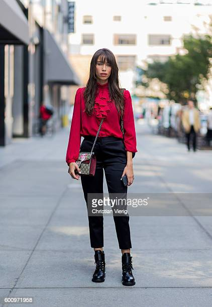 Thania Peck wearing a red blouse black pants boots and Gucci bag outside Noon By Noor on September 8 2016 in New York City