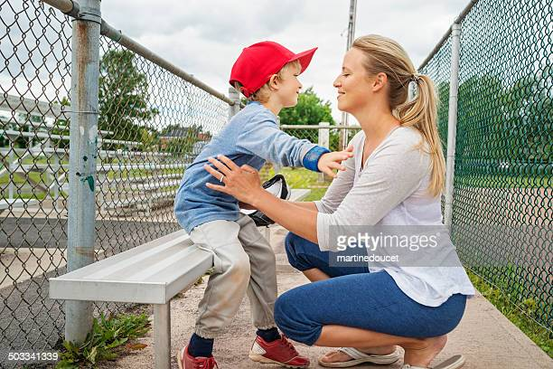 thank you mom! mother and son hugging on baseball bench. - baseball sport stock pictures, royalty-free photos & images