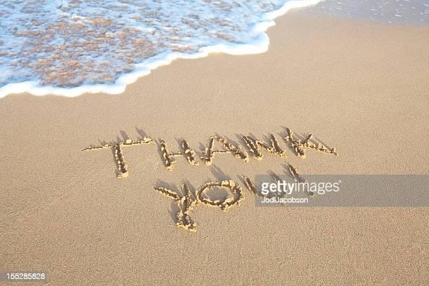 Merci écrit dans le sable sur la plage