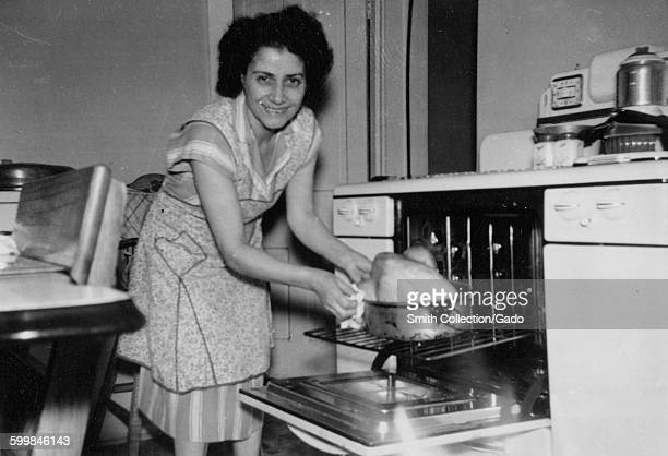 Thanksgiving Day a young woman in an apron standing in her kitchen and placing a turkey on a roasting pan into an oven smiling at the camera 1960