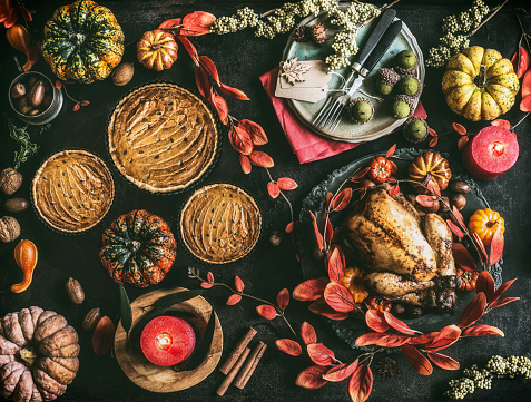 Thanksgiving day dinner table with pumpkin pie, roasted turkey and festive autumn decoration and candles - gettyimageskorea