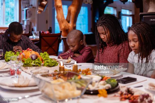 jantar de ação de graças com africano-americano família rezando - african american family dinner - fotografias e filmes do acervo