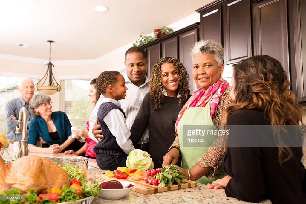 Thanksgiving:  Multi-ethnic family, friends gather in kitchen to prepare meal. : Stock Photo