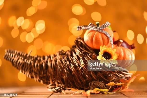 素朴な木製のテーブルの上にコルヌコピアカボチャと照らされた背景と感謝祭の静物 - 豊穣の角 ストックフォトと画像