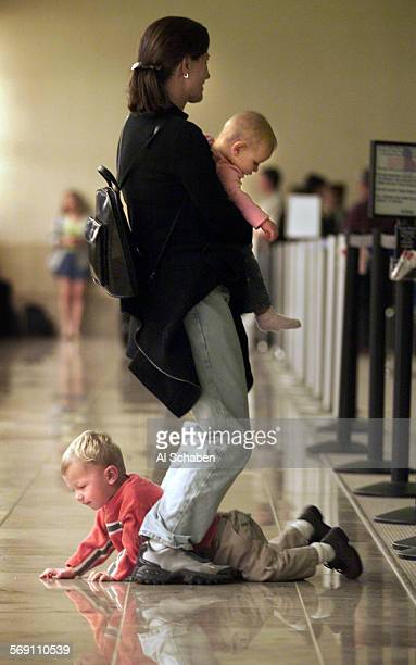 Thanksgiving traveler Marilyn Jager of Fooothill Ranch uses her feet to hold her squirming energetic two–year–old Cole while balancing her baggage...