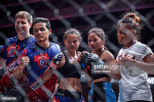 Tharoth Sam and Vy Srey Chai pose with their teams after their fight during One FC Cambodia on September 12 2014 in Phnom Penh Cambodia