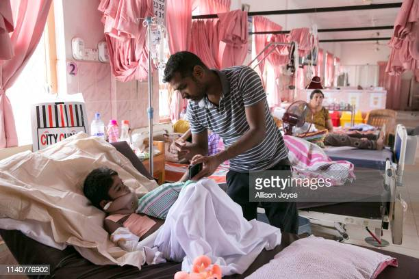 Thashan looks after his son 6 year old Shathok Shan as he is treated by a nurse on May 2 2019 in Batticaloa Sri Lanka Thashan lost his wife and...