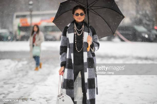 Thassia Naves is seen wearing black white plaid coat necklace black pants white Chanel backpack outside Chanel during Haute Couture Spring Summer...