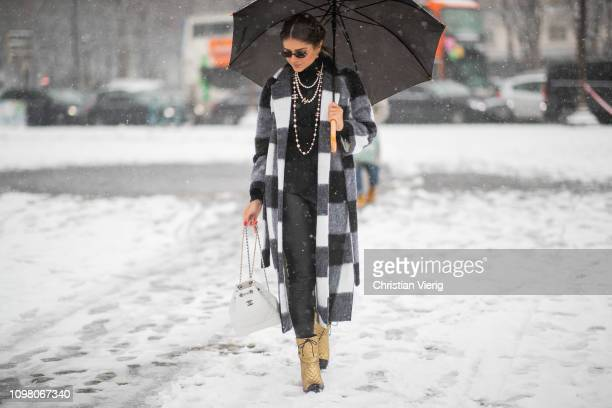 Thassia Naves is seen wearing black white plaid coat necklace black pants golden Chanel boots white Chanel backpack outside Chanel during Haute...
