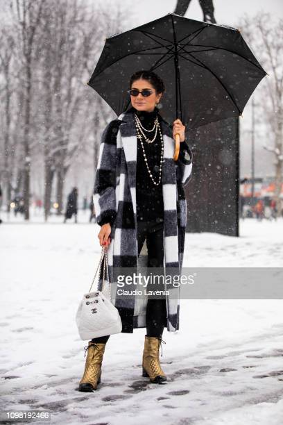 Thassia Naves wearing a black and white checked coat gold Chanel boots and white Chanel bag is seen outside Chanel show during Paris Fashion Week...