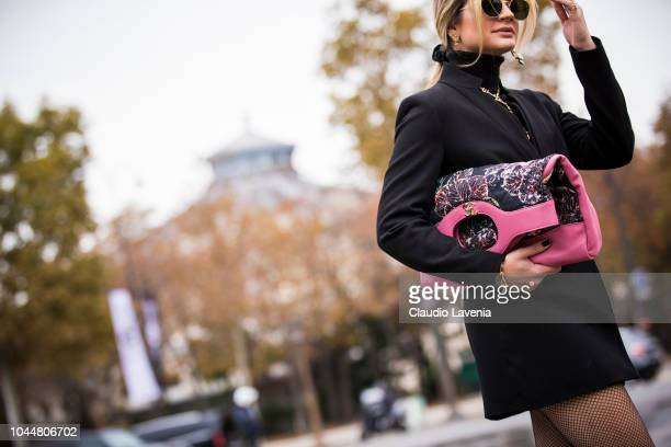 Thassia Naves wearing a black coat Chanel necklace and oversized Chanel pink printed clutch is seen before the Chanel show on October 2 2018 in Paris...