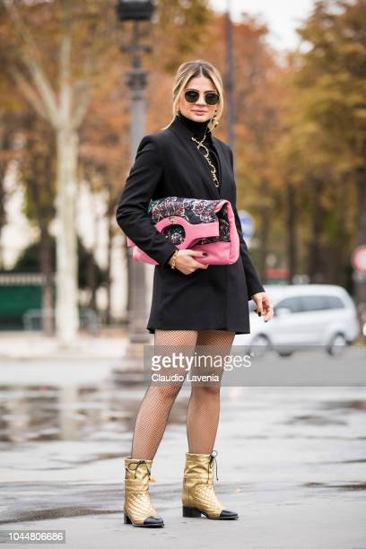 Thassia Naves wearing a black coat Chanel necklace gold boots and oversized Chanel pink printed clutch is seen before the Chanel show on October 2...