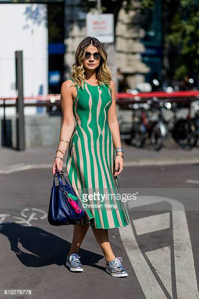 Thassia Naves wearing a green striped Lucas Magalhaes dress navy Loewe bag and Arezzo shoes outside Jil Sander during Milan Fashion Week...