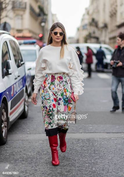 Thassia Naves wearing a skirt with floral print ruffled knit red boots outside Moncler on March 7 2017 in Paris France