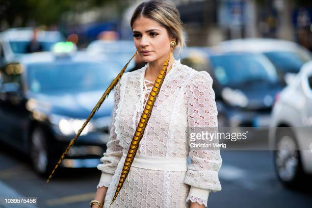 Thassia Naves wearing long feather earrings white sheer dress is seen outside Gucci during Paris Fashion Week Womenswear Spring/Summer 2019 on...