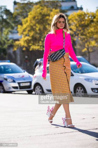 Thassia Naves wearing neon pink turtleneck sweater checked skirt printed crossbody bag and white Prada flame leather sandals is seen before the...