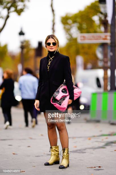 Thassia Naves wears a black dress a pink Chanel bag outside Chanel during Paris Fashion Week Womenswear Spring/Summer 2019 on October 2 2018 in Paris...