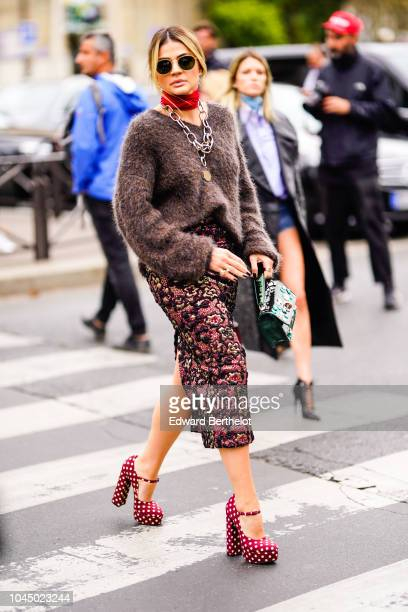 Thassia Naves wears a brown wool pullover a green bag a floral print skirt red shoes a chain necklace a red choker outside Miu Miu during Paris...