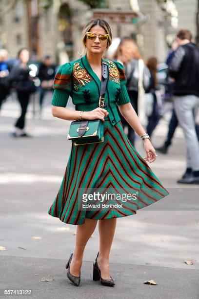 Thassia Naves wears a green shirt a green Prada bag a striped skirt outside Miu Miu during Paris Fashion Week Womenswear Spring/Summer 2018 on...
